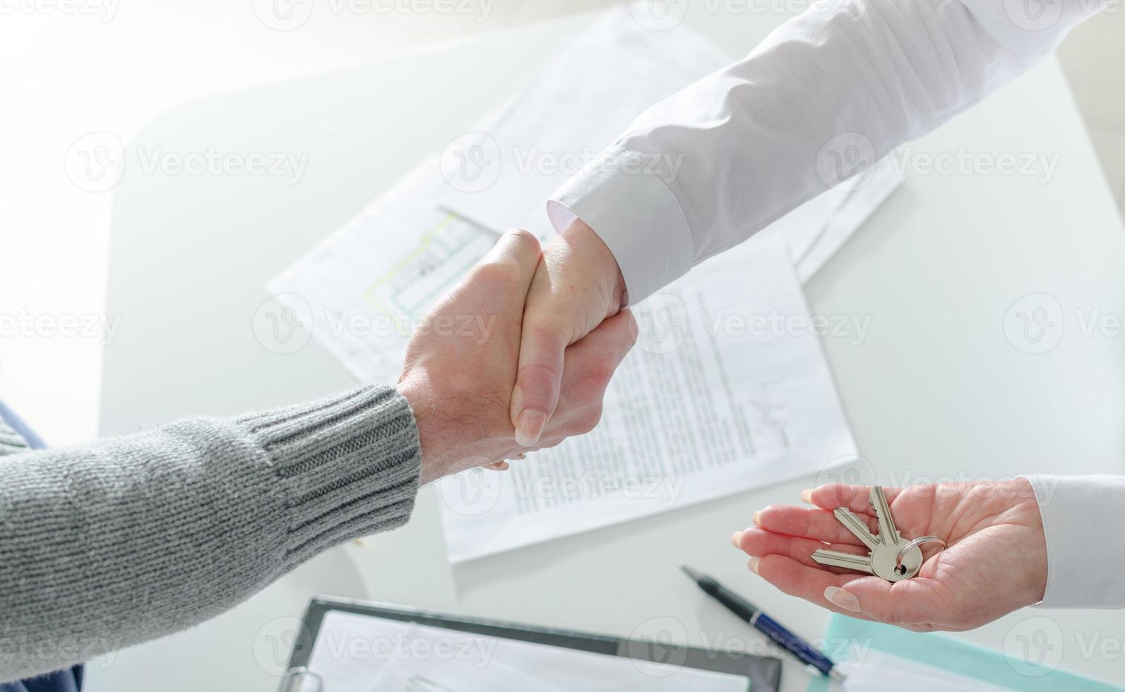 Maklerin schüttelt ihrem Kunden die Hand foto