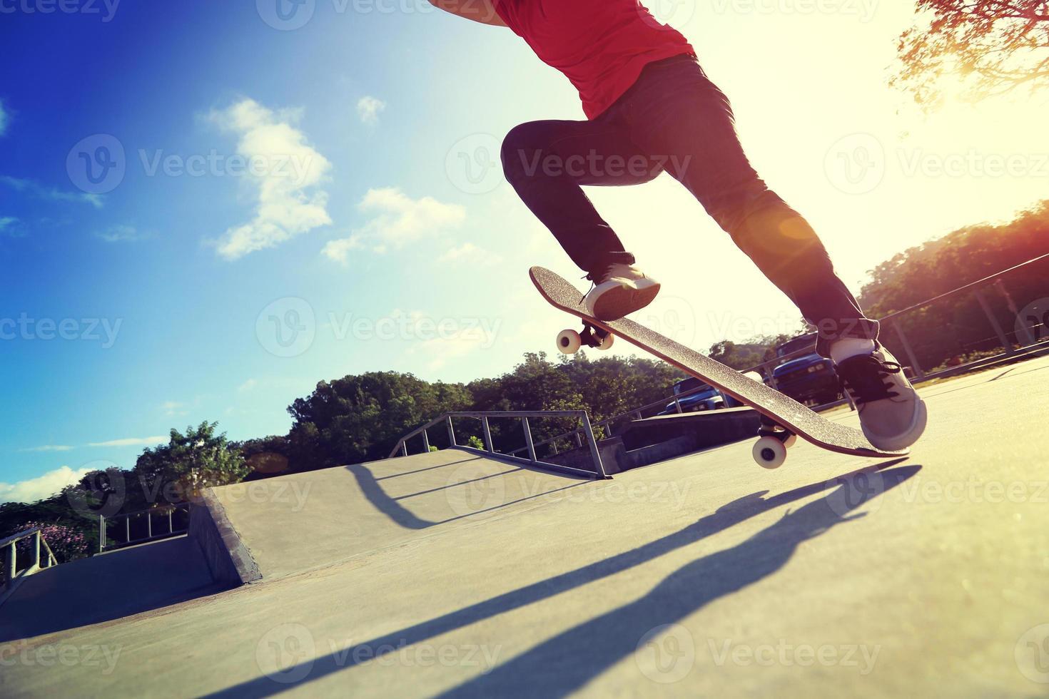 Skateboarder Beine machen einen Trick ollie im Skatepark foto