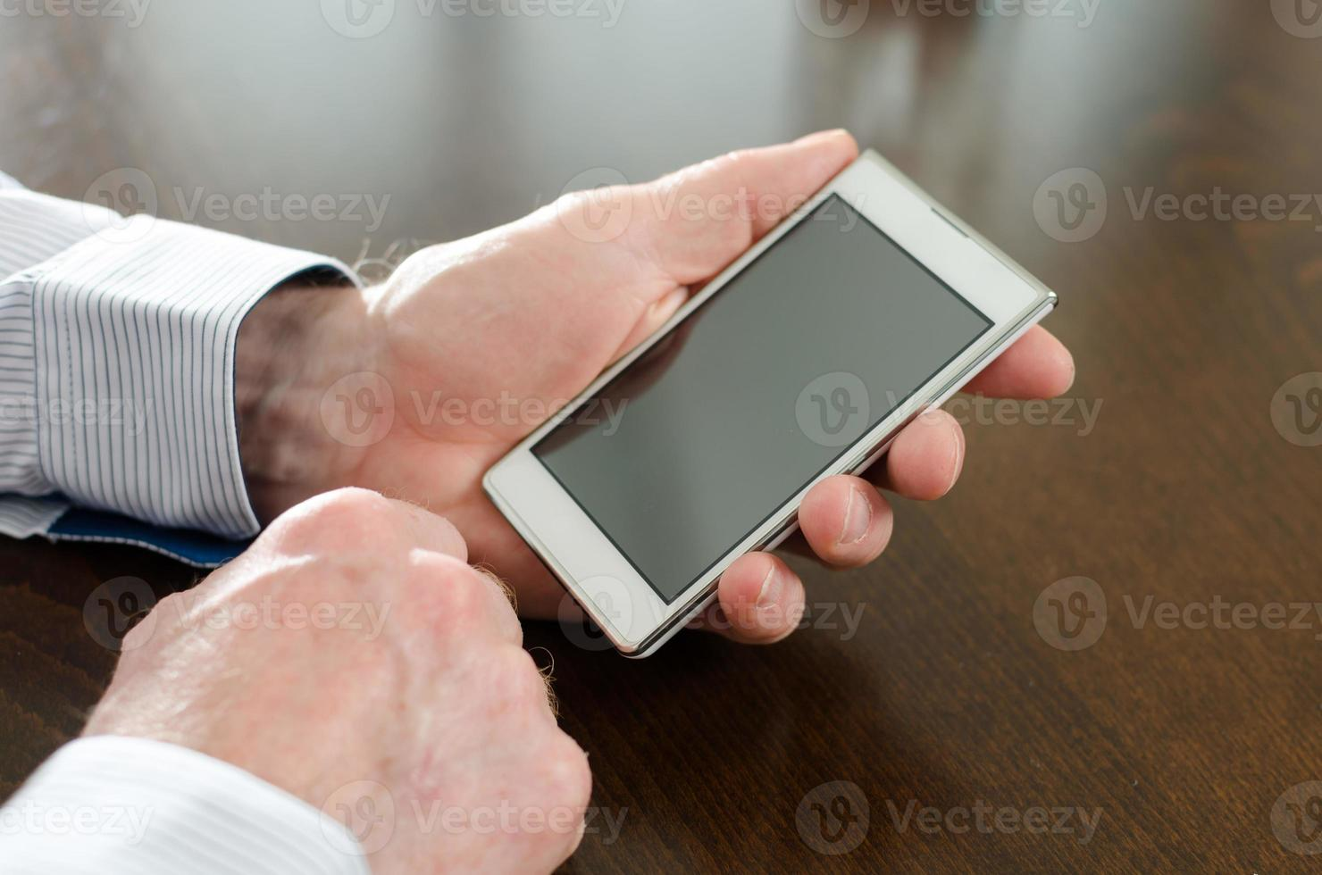 Mann hält sein Smartphone foto