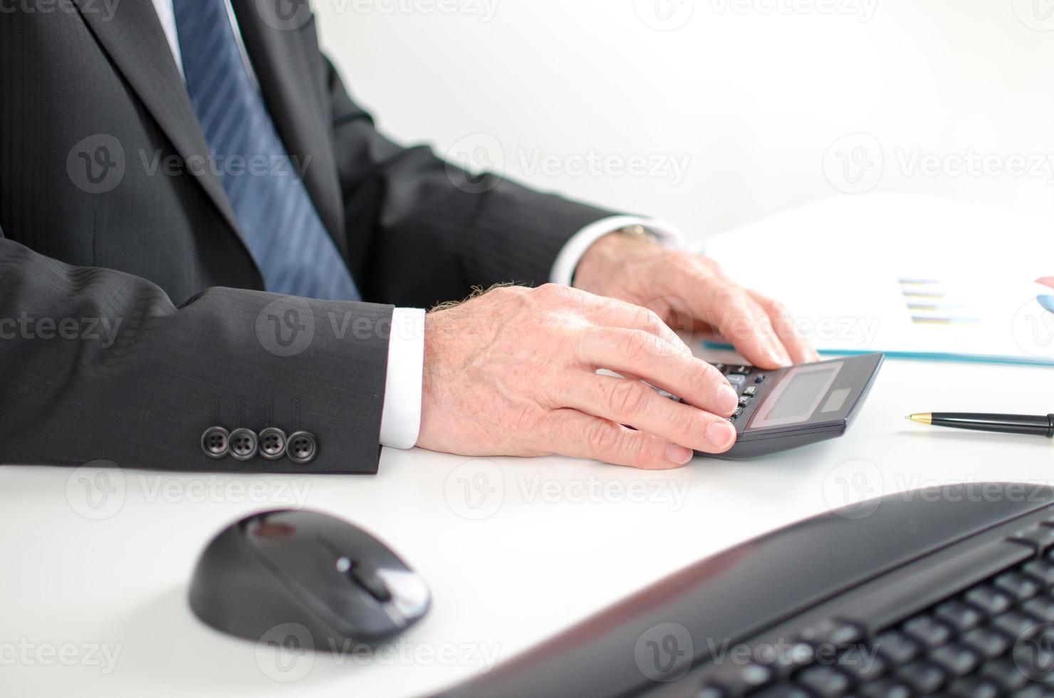 Geschäftsmann, der Finanzergebnisse berechnet foto
