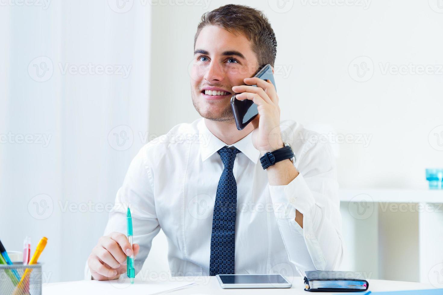 junger hübscher Mann, der in seinem Büro mit Handy arbeitet. foto