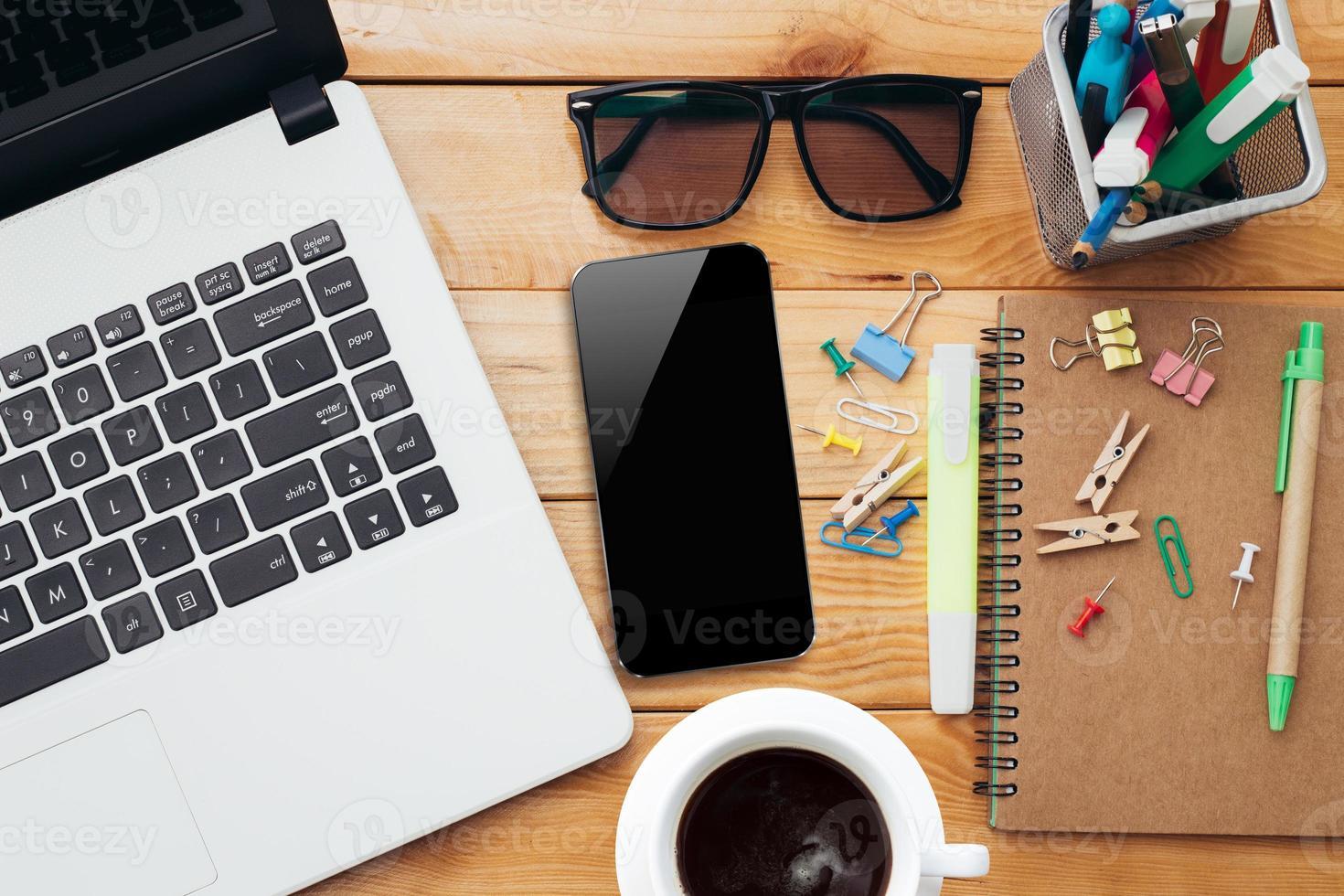 Arbeitsplatz mit Laptop Kaffeetelefon und Notebook foto