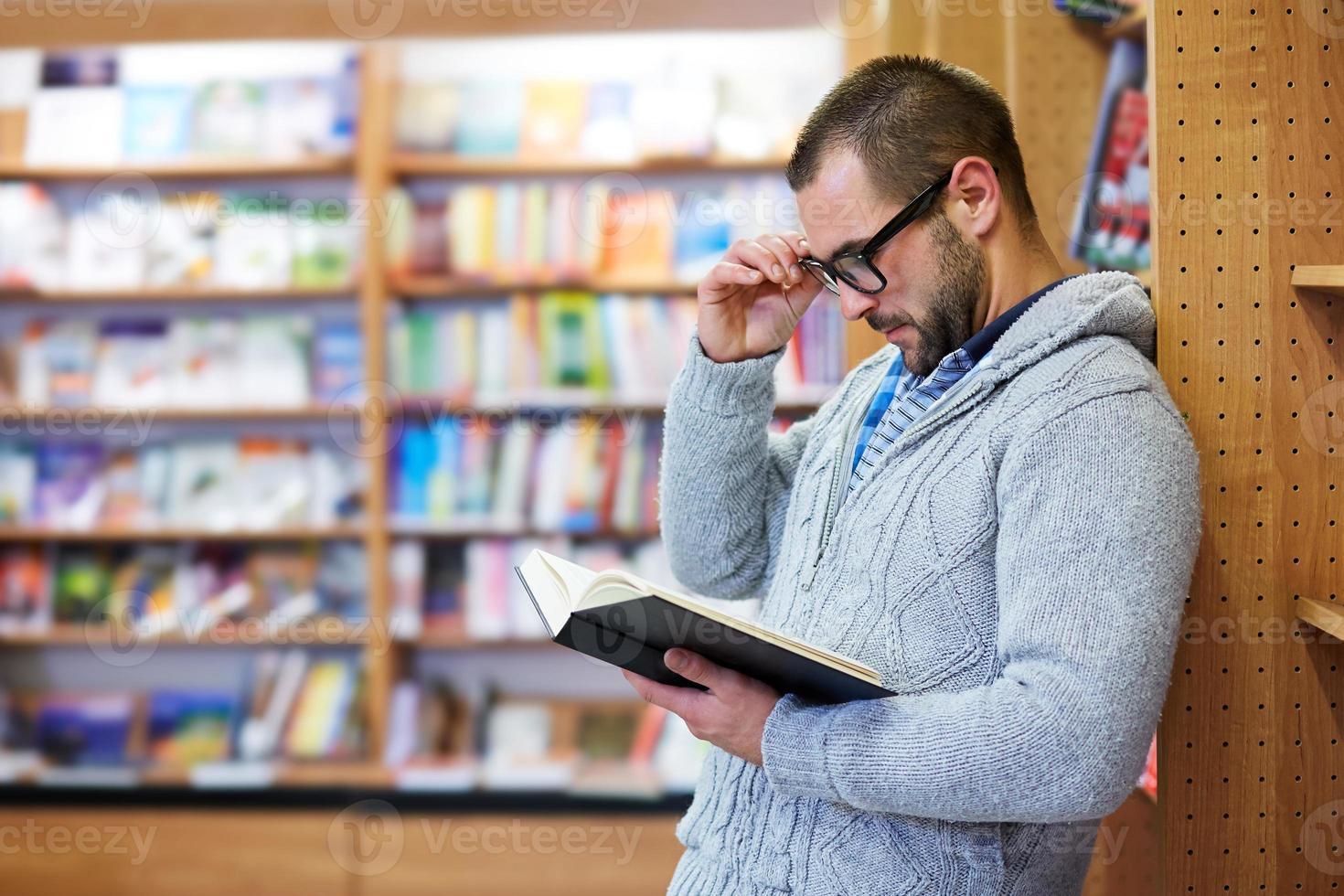 Mann liest in der Bibliothek foto