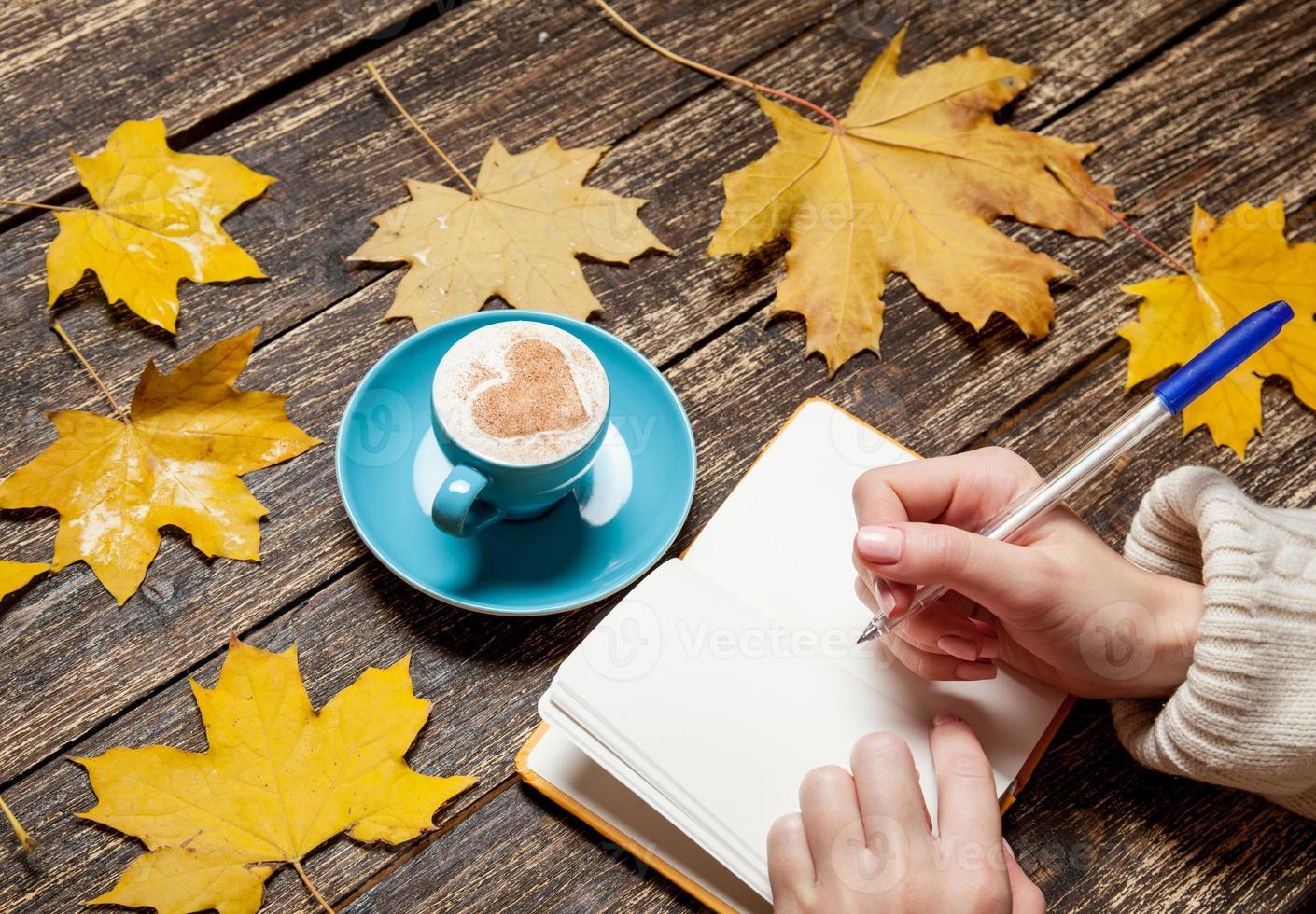 weibliche Hand, die etwas in Notizbuch nahe Tasse Kaffee schreibt. foto