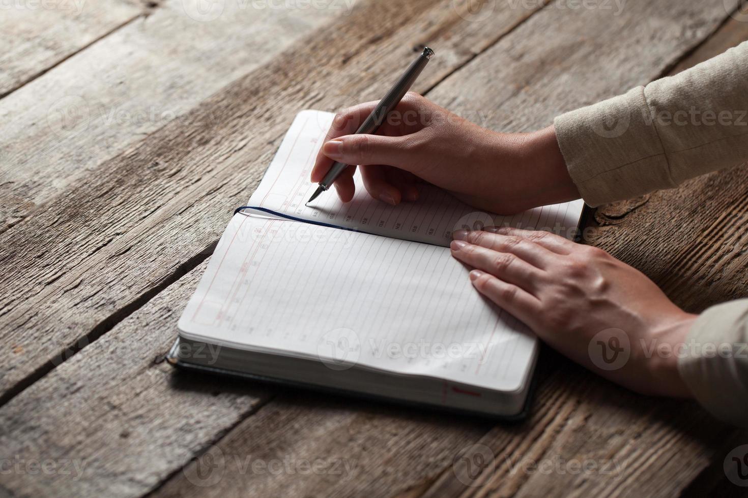 Hand schreibt mit einem Stift in ein Notizbuch foto