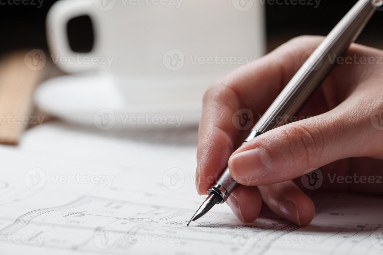 Frau, die einen Stift über einem Hausbauplan hält foto