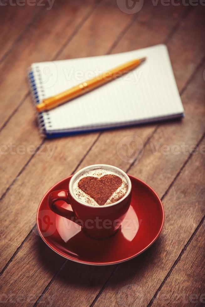 Tasse Kaffee mit Notizbuch auf einem Holztisch. foto