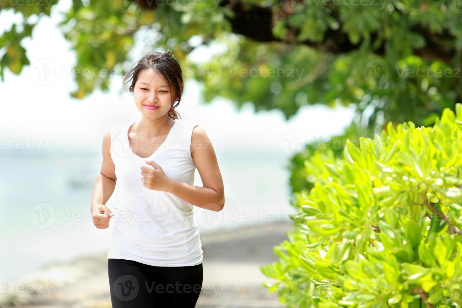 Mädchen, das am Strand joggt foto