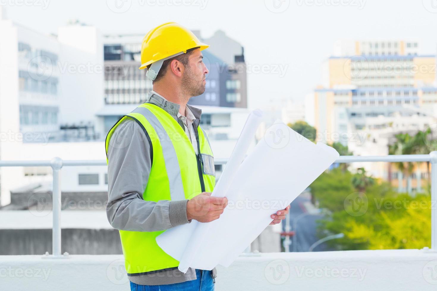 Architekt in schützender Arbeitskleidung, die Blaupausen im Freien hält foto