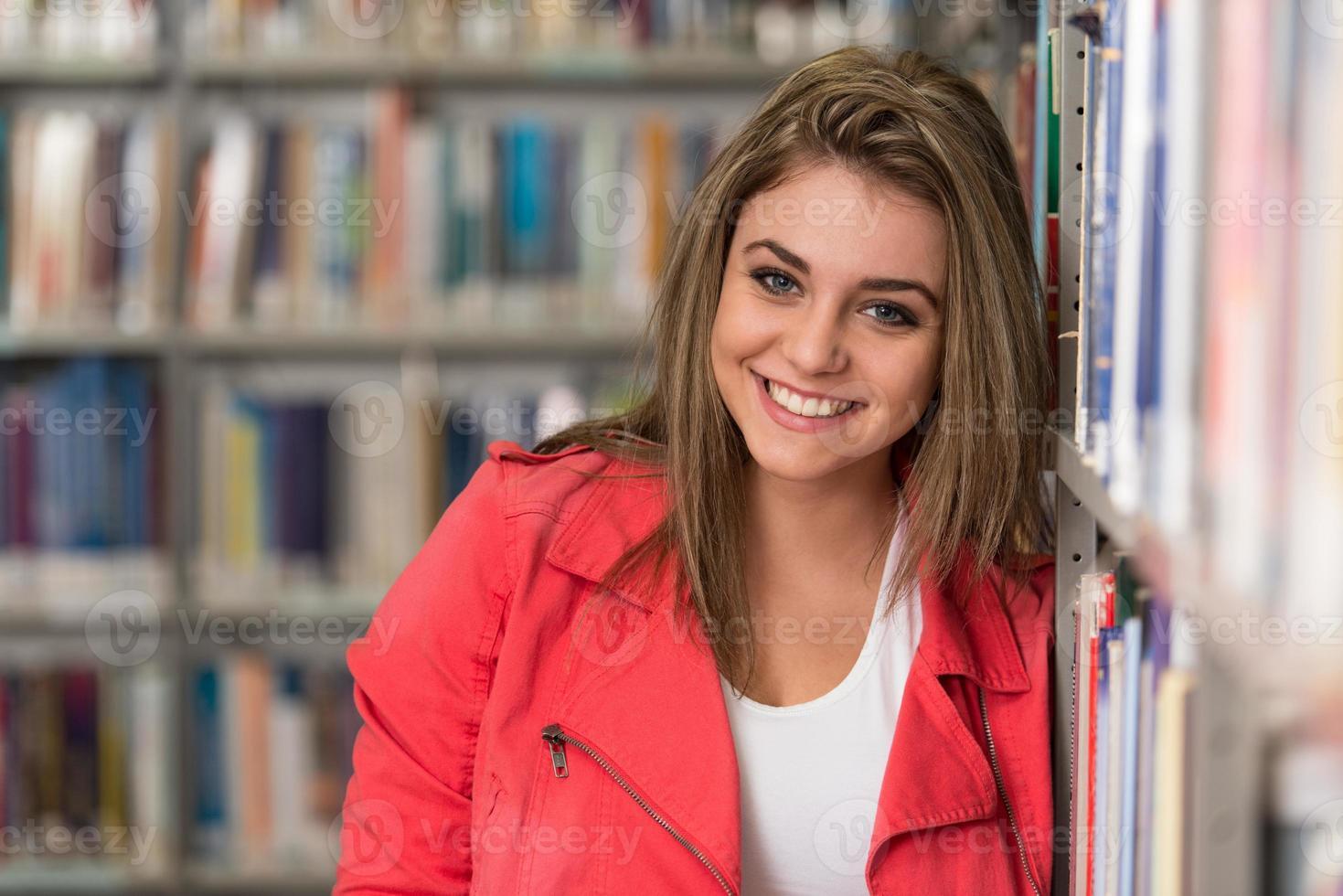 Porträt des glücklichen lächelnden jungen brünetten Studentenmädchens foto