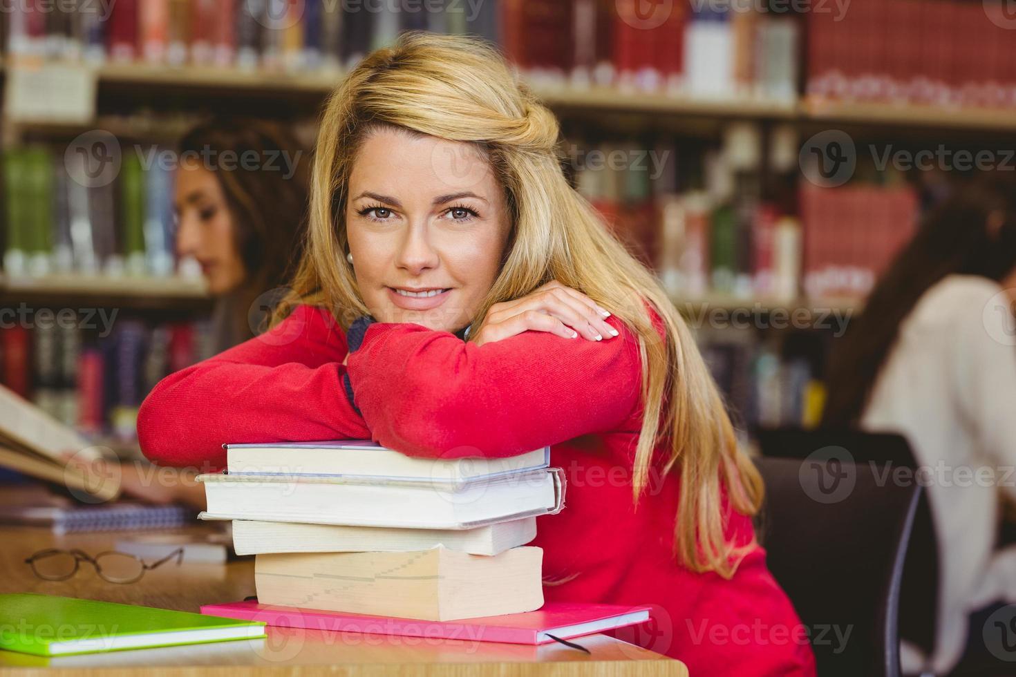 lächelnder reifer Student, der sich auf einen Stapel Bücher stützt foto