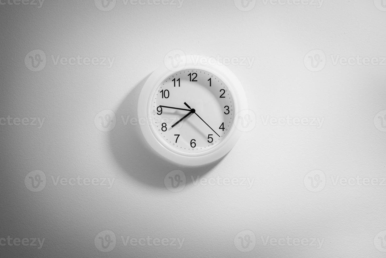 Schwarzweiss-Uhr, die an der Wand mit Raum hängt foto
