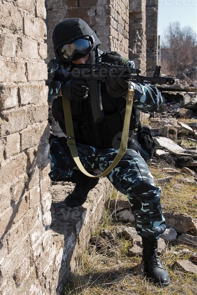 Soldat zielt mit automatischem Gewehr foto