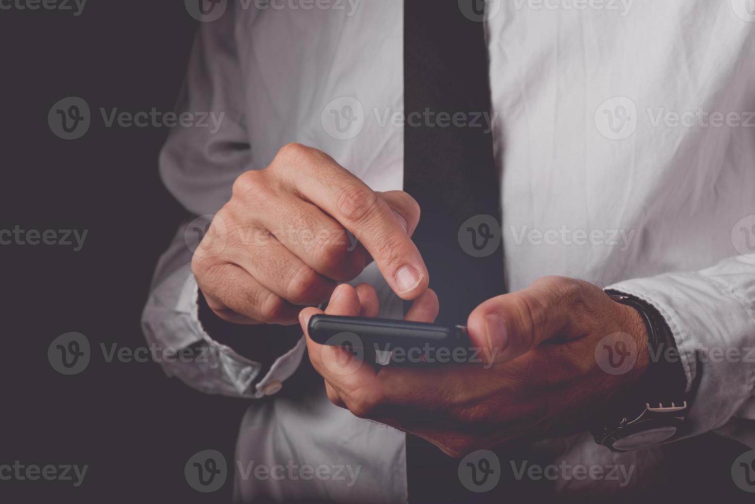 Geschäftsmann, der am mobilen Smartphone arbeitet foto