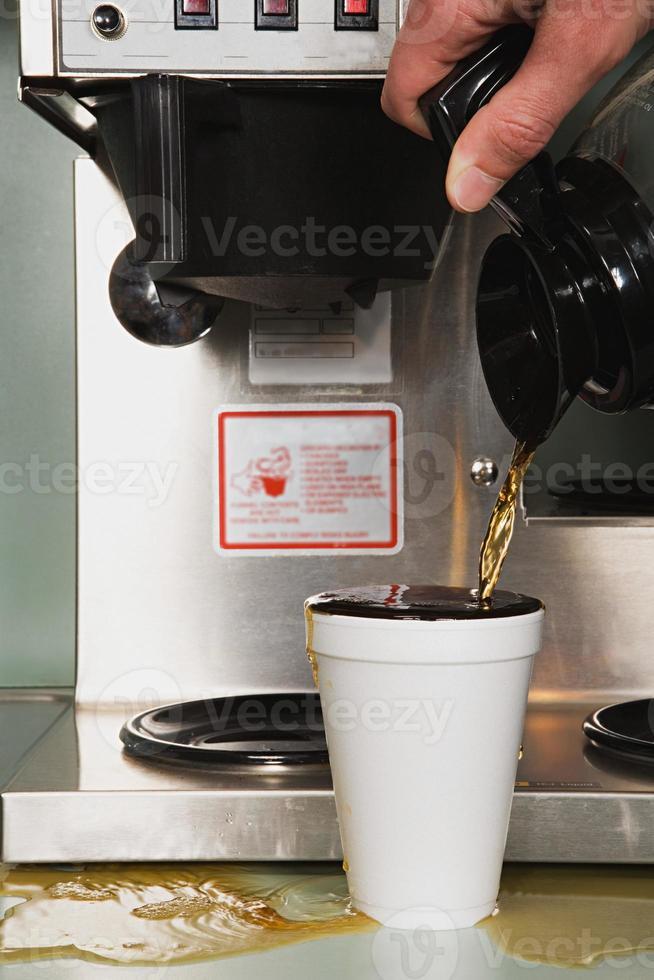 Geschäftsmann gießt einen Kaffee ein foto