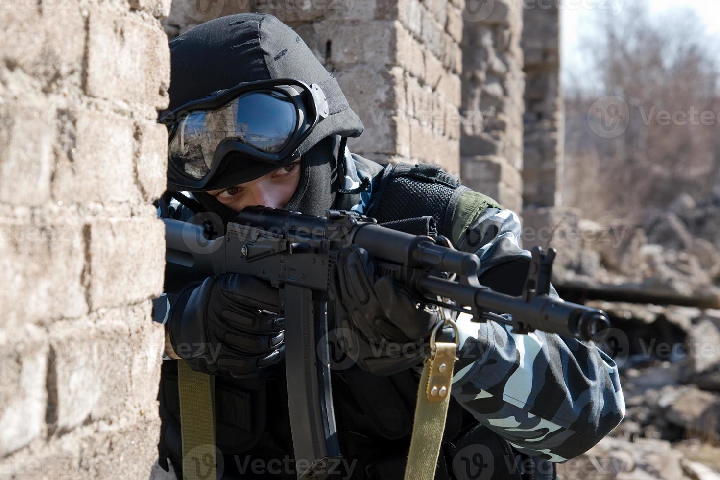 Soldat, der mit einem automatischen Gewehr auf ein Ziel zielt foto