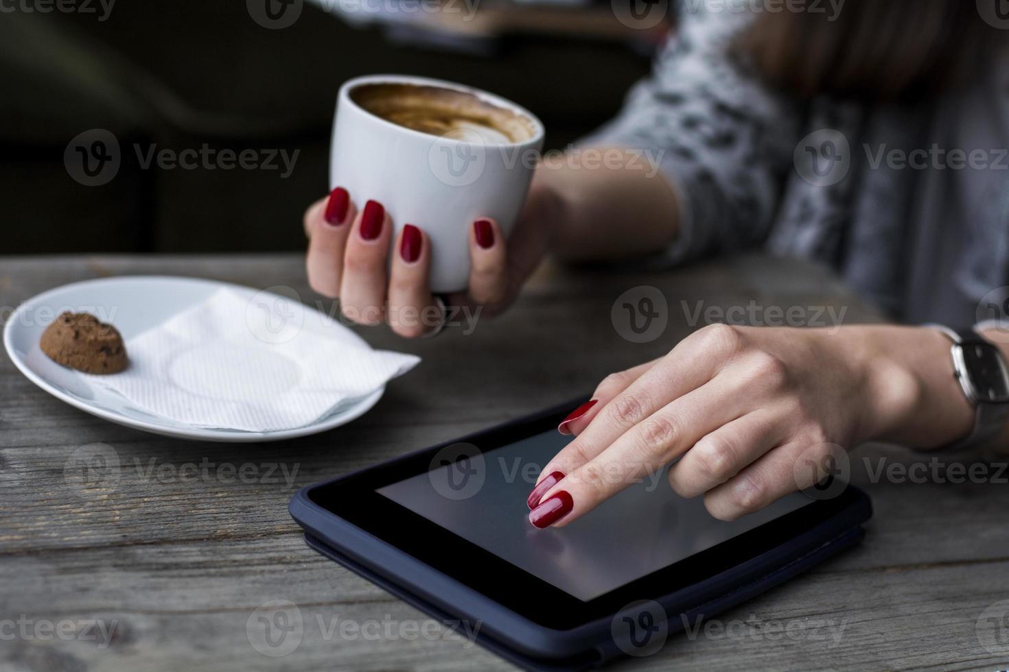 Frauenhand, die auf Tablette stöbert und Kaffee hält foto