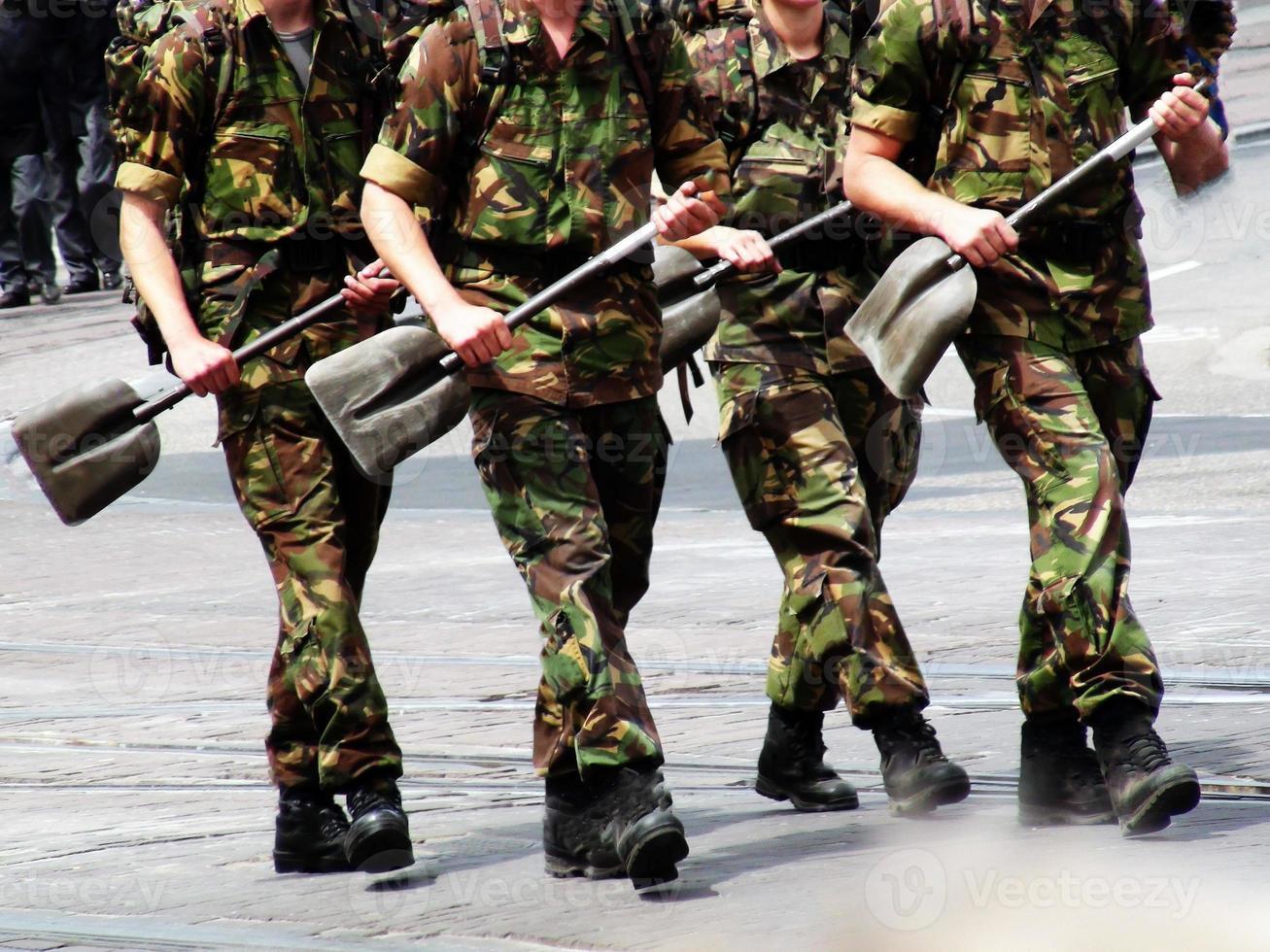 Soldaten marschieren mit Bauschaufel foto