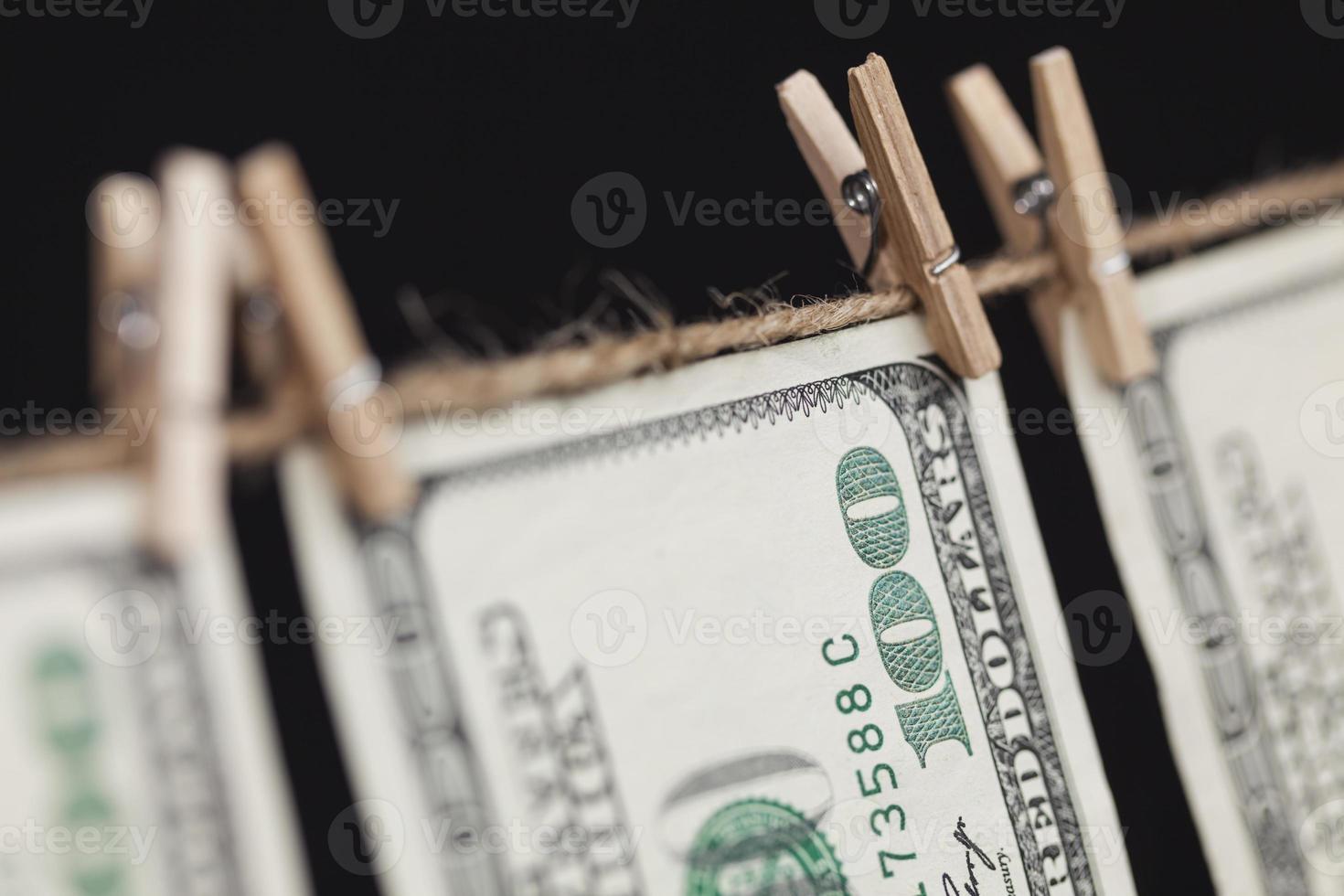 Hundert-Dollar-Scheine hängen von der Wäscheleine auf dunklem Hintergrund foto