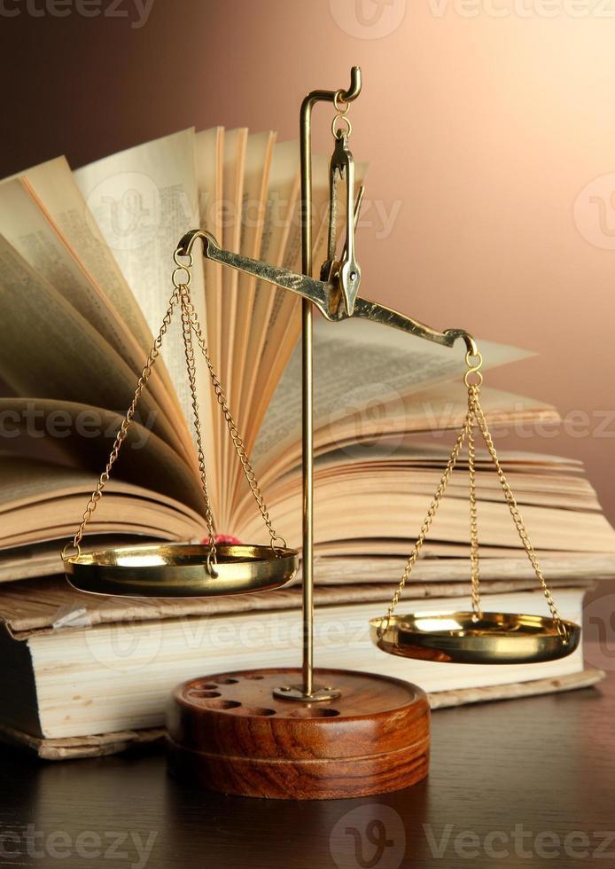 Goldschuppen der Gerechtigkeit und Bücher auf braunem Hintergrund foto