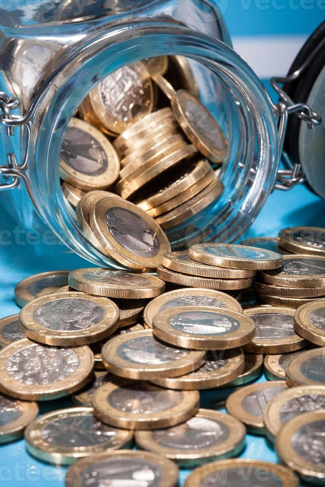Aus dem Glas verschüttete Euro-Münzen foto