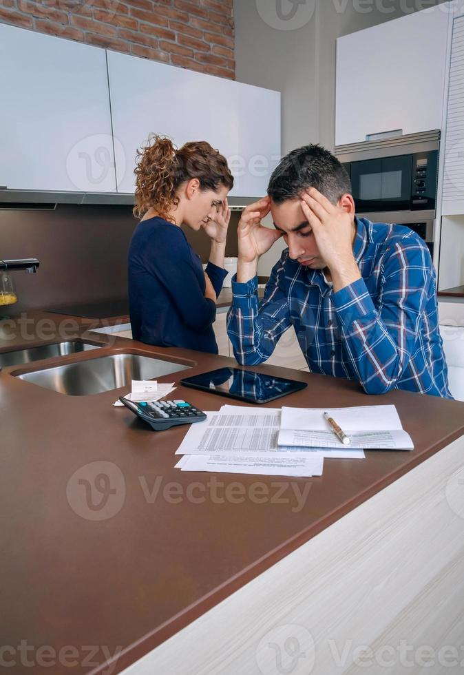 verzweifeltes junges Paar mit Schulden, die ihre Rechnungen überprüfen foto