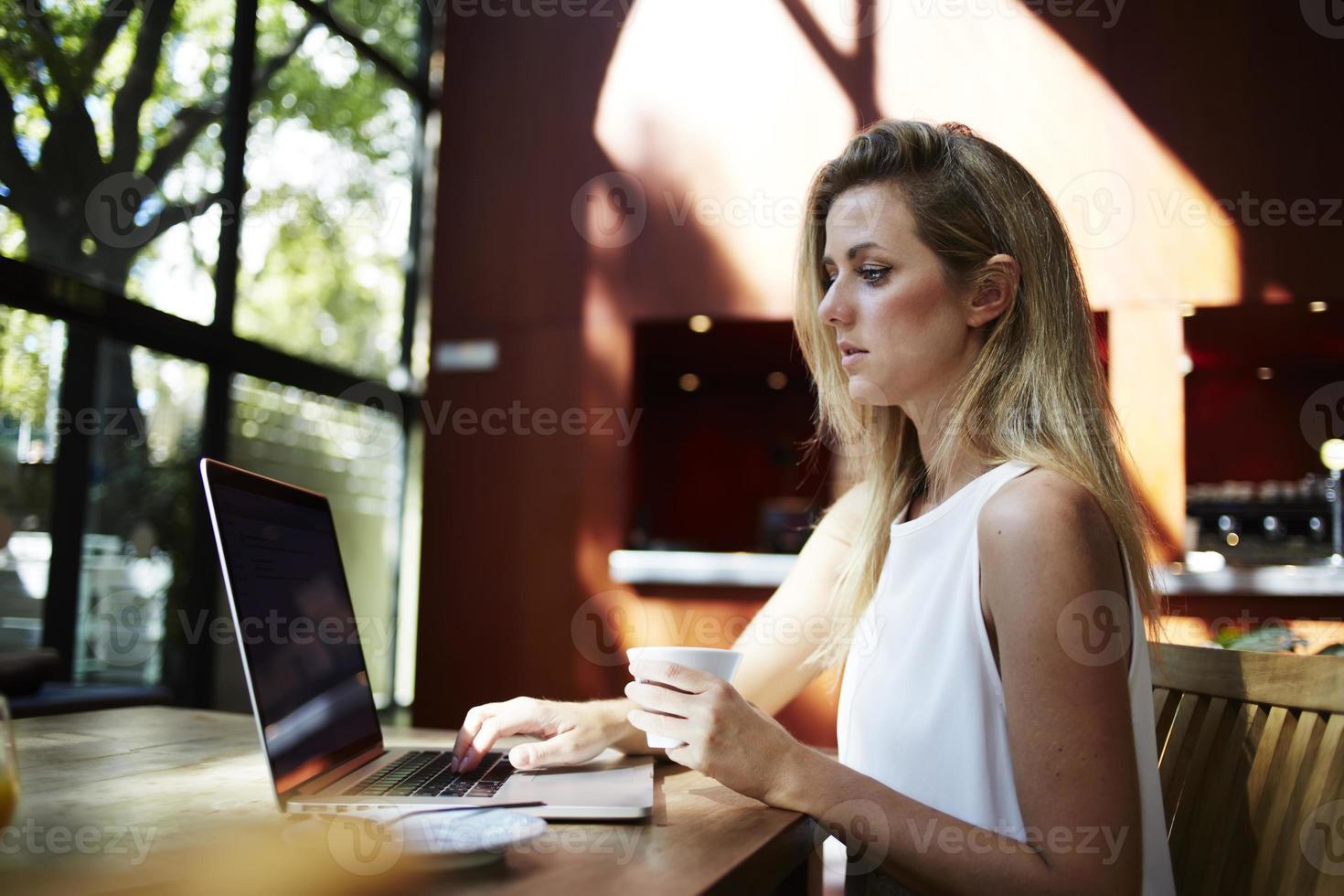 Frau, die Tasse Kaffee hält, während Text auf Netzbuch liest foto