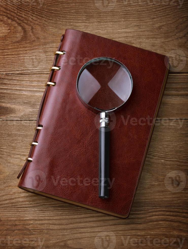 Notizbuch mit einer Lupe auf Holztisch foto
