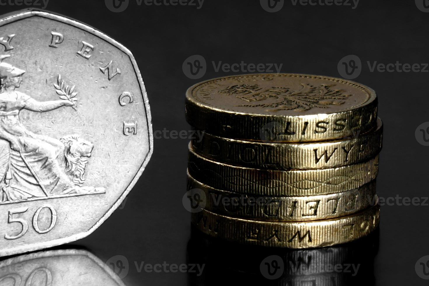 Studioaufnahme von britischen Münzen auf schwarzem Hintergrund foto