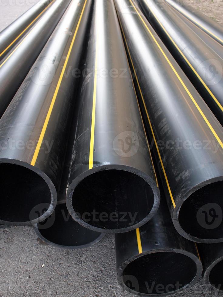 schwarzes Plastik-PVC-Rohr, das auf der Straße liegt foto