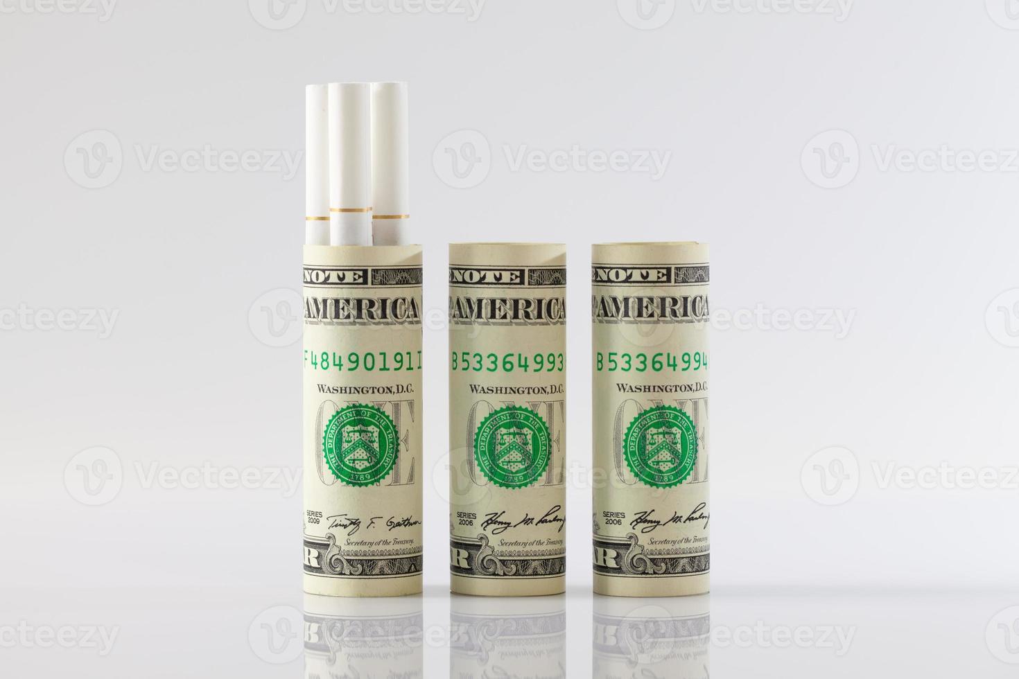 Rollen mit Dollarnoten und langen Zigaretten foto