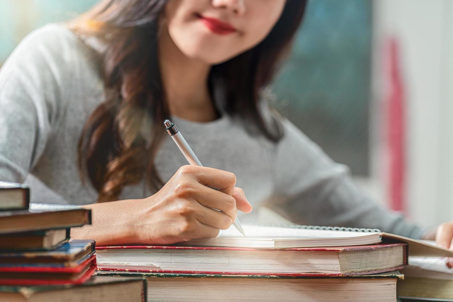Ein junger asiatischer Student, der Hausaufgaben in einer Bibliothek macht foto