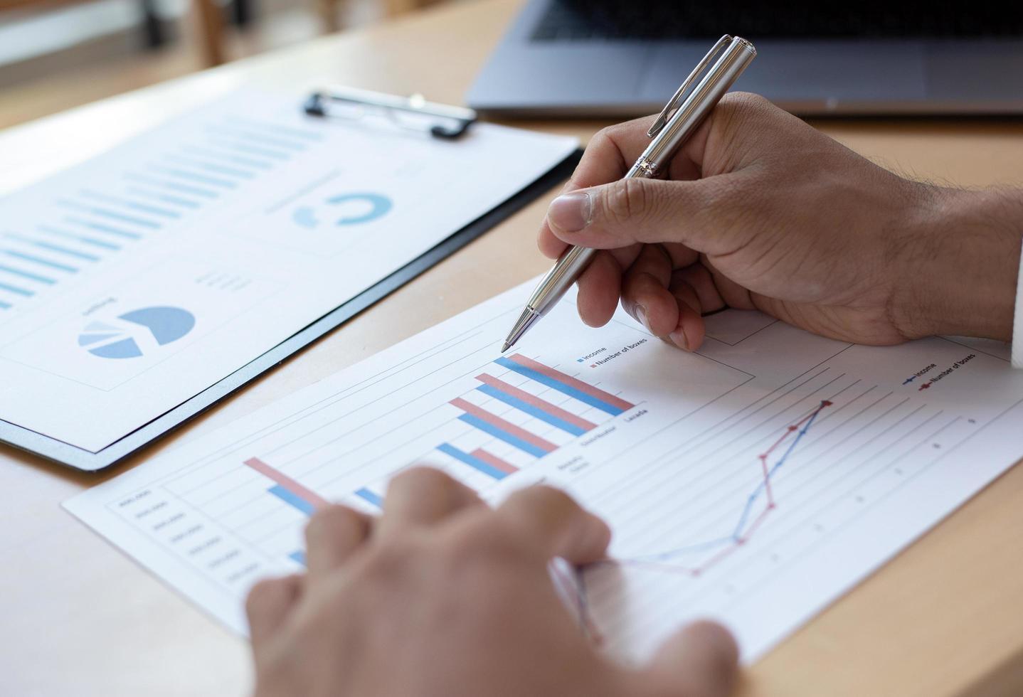 Geschäftsmann, der Finanzdiagramm am Schreibtisch studiert foto