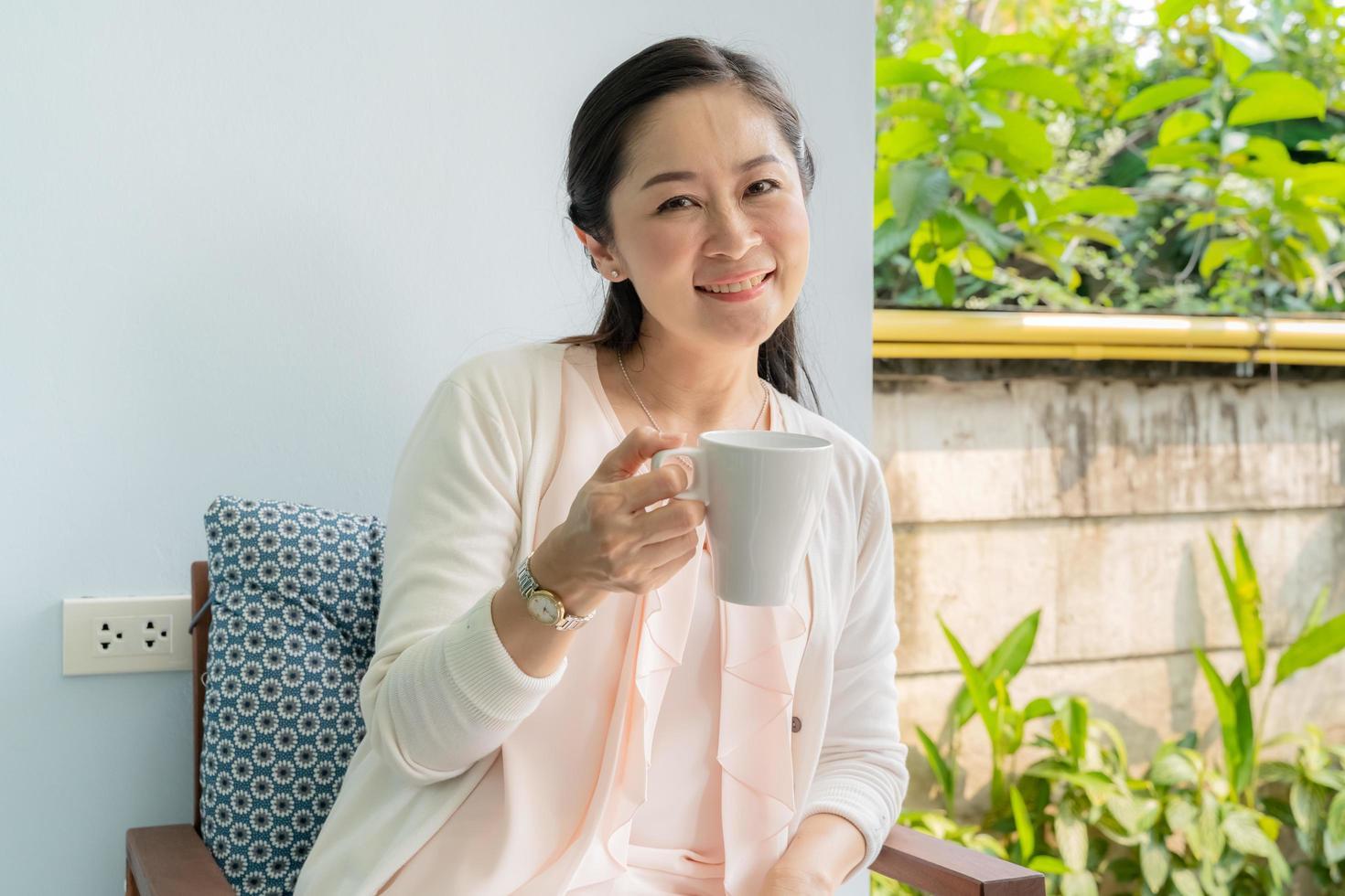 asiatische Frau mittleren Alters, die im Hinterhof sitzt und Kaffee nippt. foto