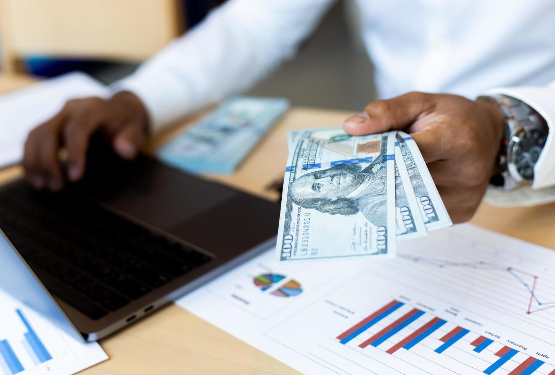 Geschäftsmann, der Bargeld mit Finanzdiagramm am Schreibtisch zählt foto