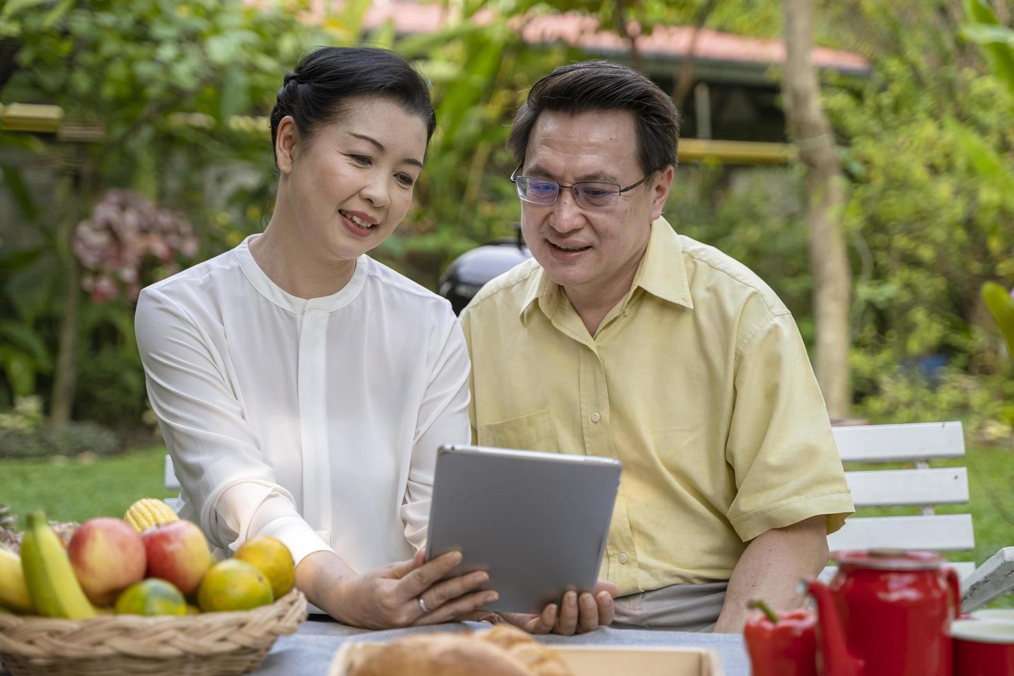 älteres Ehepaar sitzt draußen und beobachtet Tablet-Bildschirm foto