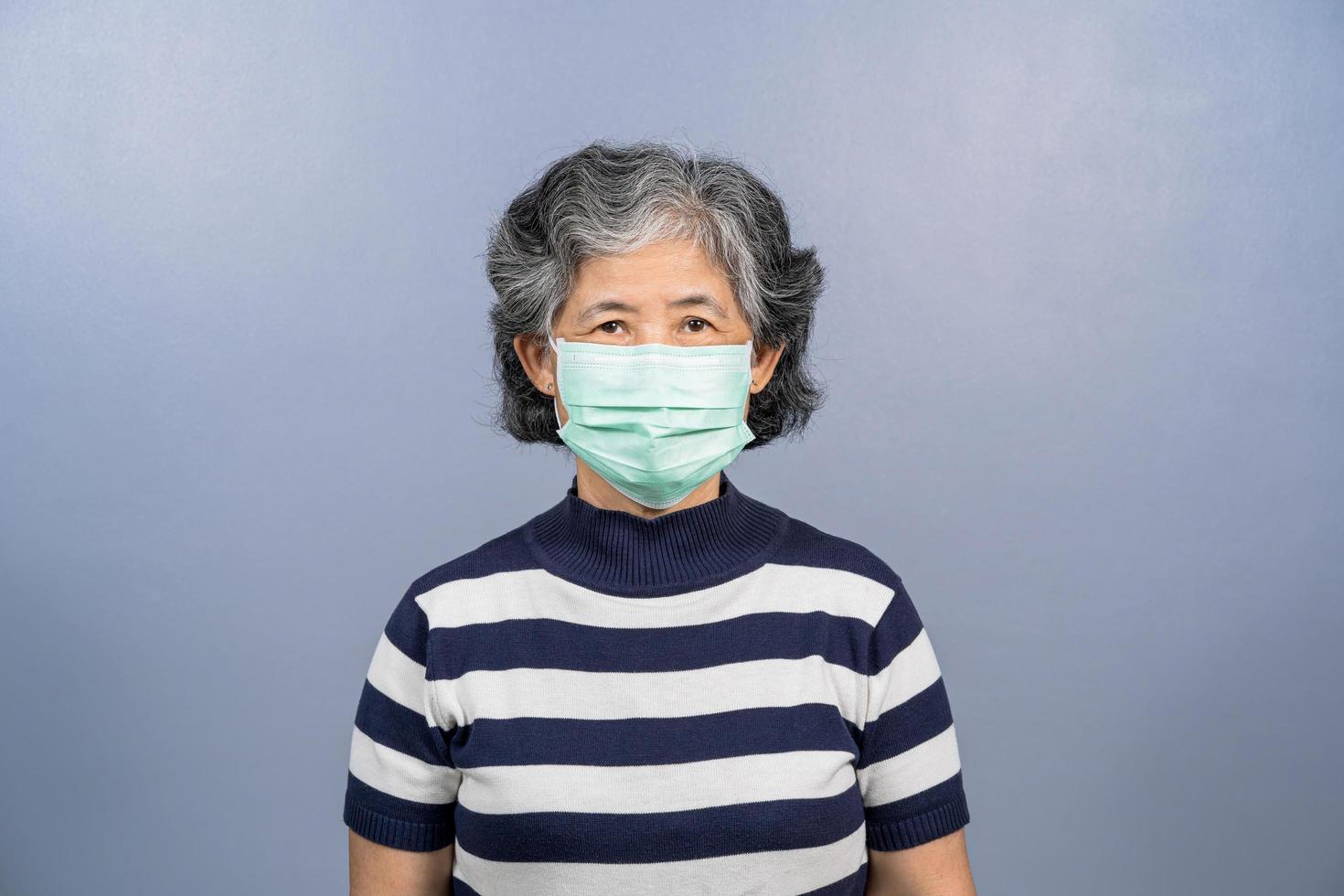 eine ältere asiatische Frau, die chirurgische Maske auf festem Hintergrund trägt foto