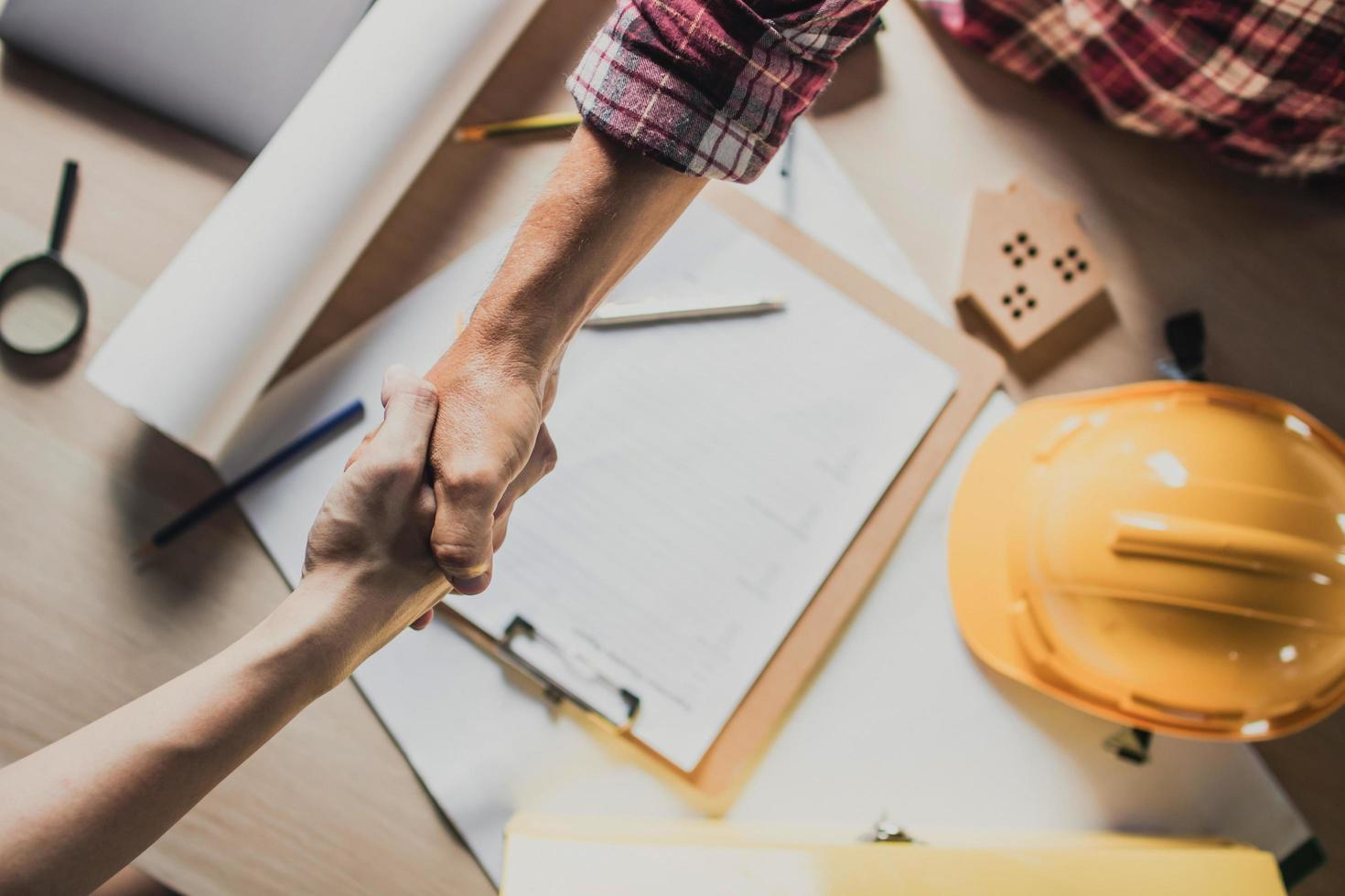 Ein Ingenieur und ein Bauunternehmer geben einem Bauangebot die Hand foto