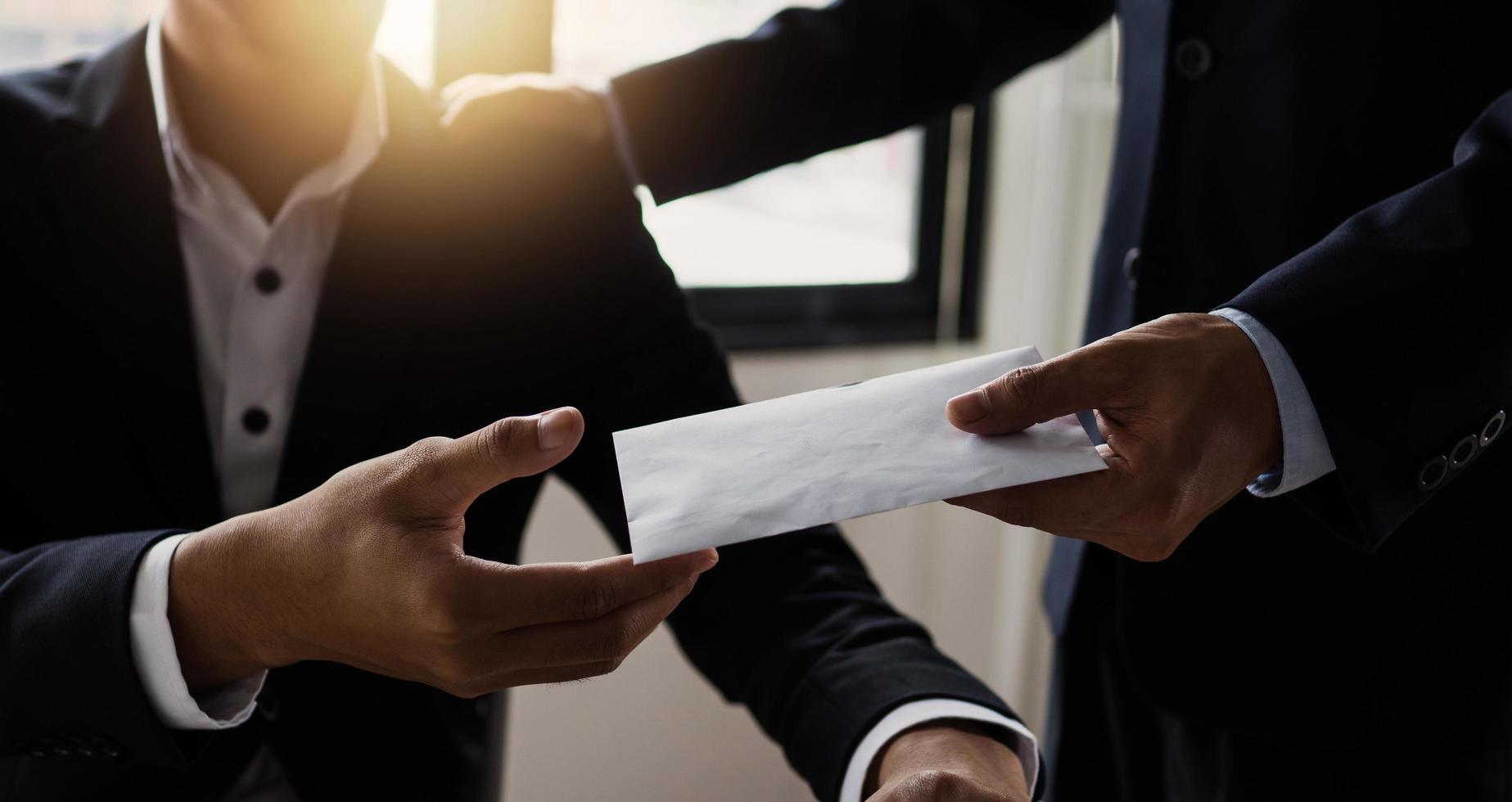 Fensterbeleuchtete Szene von zwei Geschäftsleuten, die einen Umschlag austauschen foto