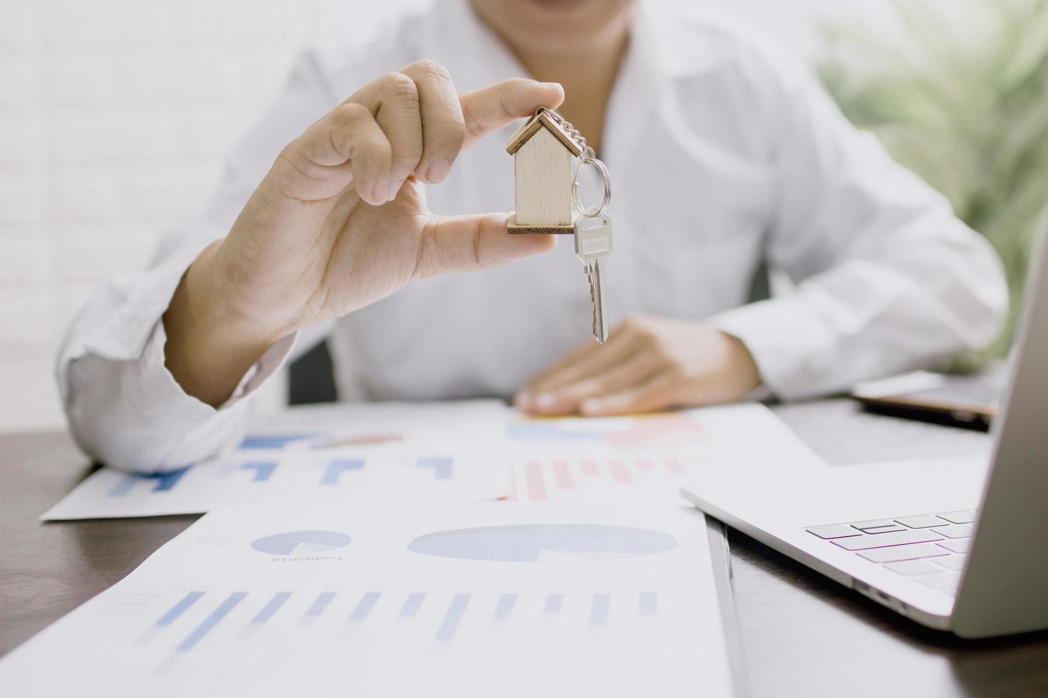 Immobiliengeschäftsmann, der Schlüsselbund des Modellhauses hält foto