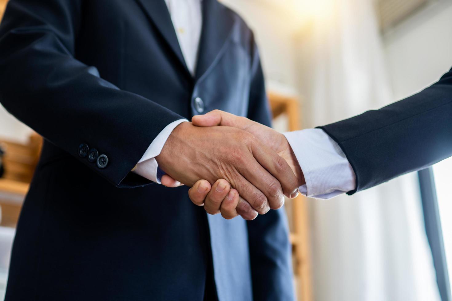 Zwei Geschäftsleute geben sich die Hand, um einen Verhandlungsvertrag bei der Arbeit zu besiegeln foto