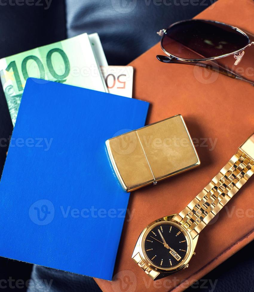 Reiseaccessoire, Reisepass, Geld, goldene Uhr, Sonnenbrille und Feuerzeug foto