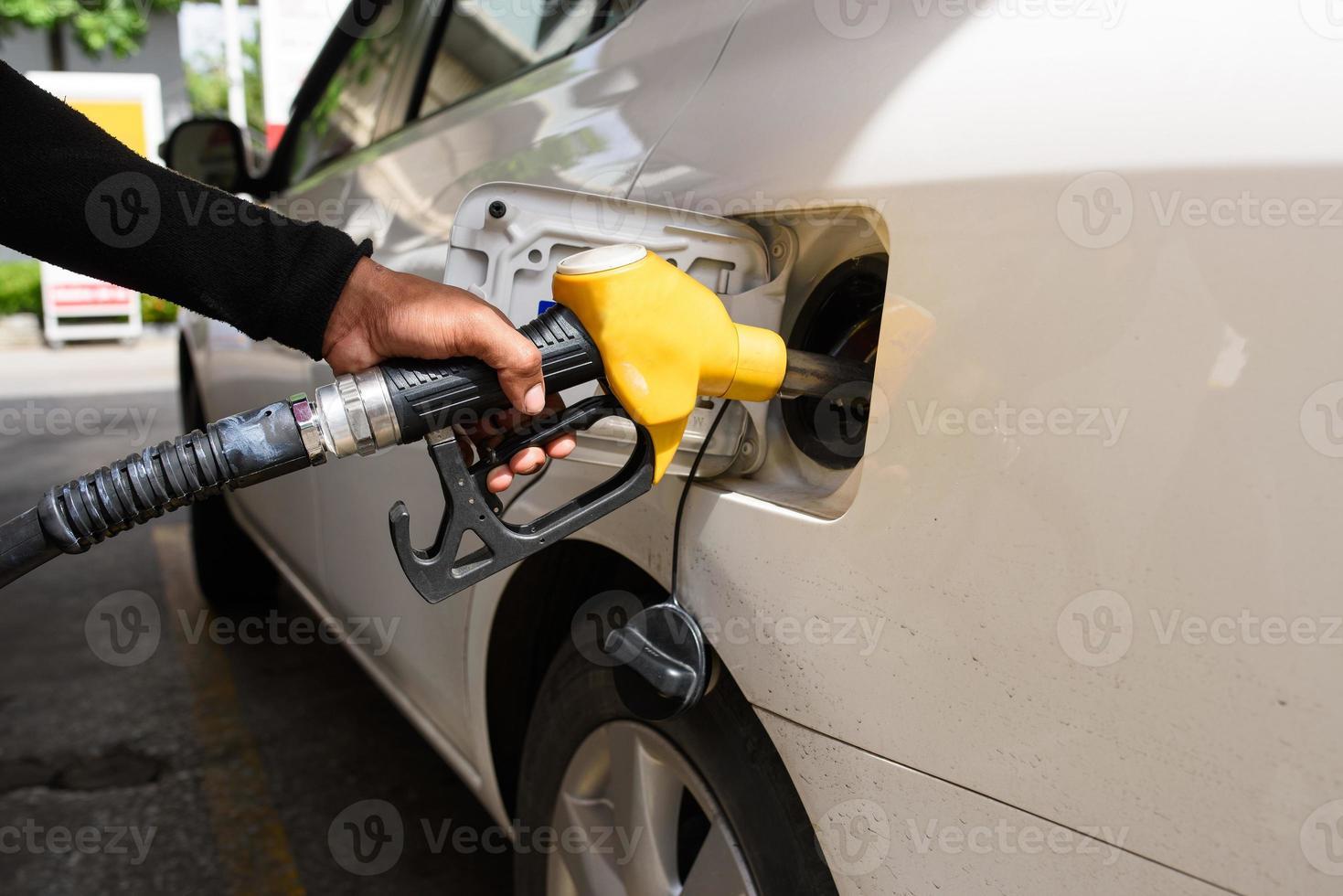 Hand das Auto mit Kraftstoff auffüllen, Hand fokussieren foto