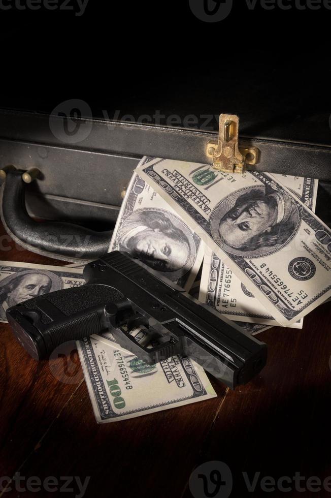 Waffe und Dollarschein in Aktentasche. foto
