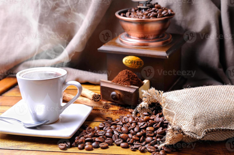 Zusammensetzung mit einer Tasse Kaffee, Bohnen und Kaffeemühle foto