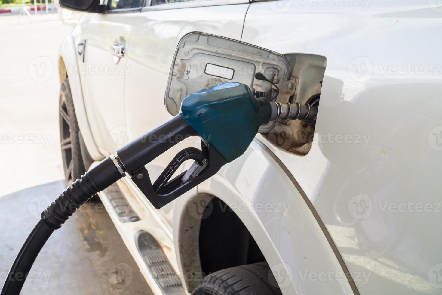 Füllen Sie das weiße Auto mit Feul am Benzin nach foto