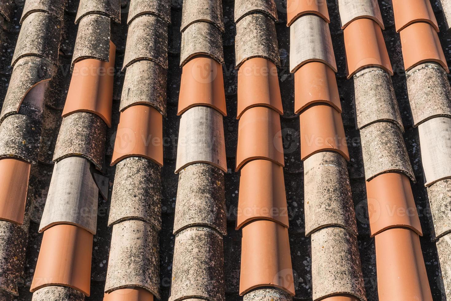 Neue Terrakottafliesen auf einem verwitterten Dach foto