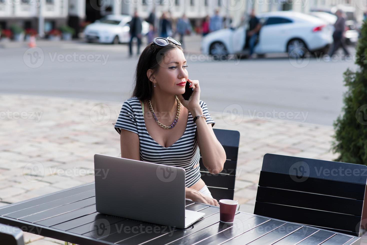 Geschäftsfrau, die auf Handy während der Arbeit am tragbaren Netzbuch spricht foto