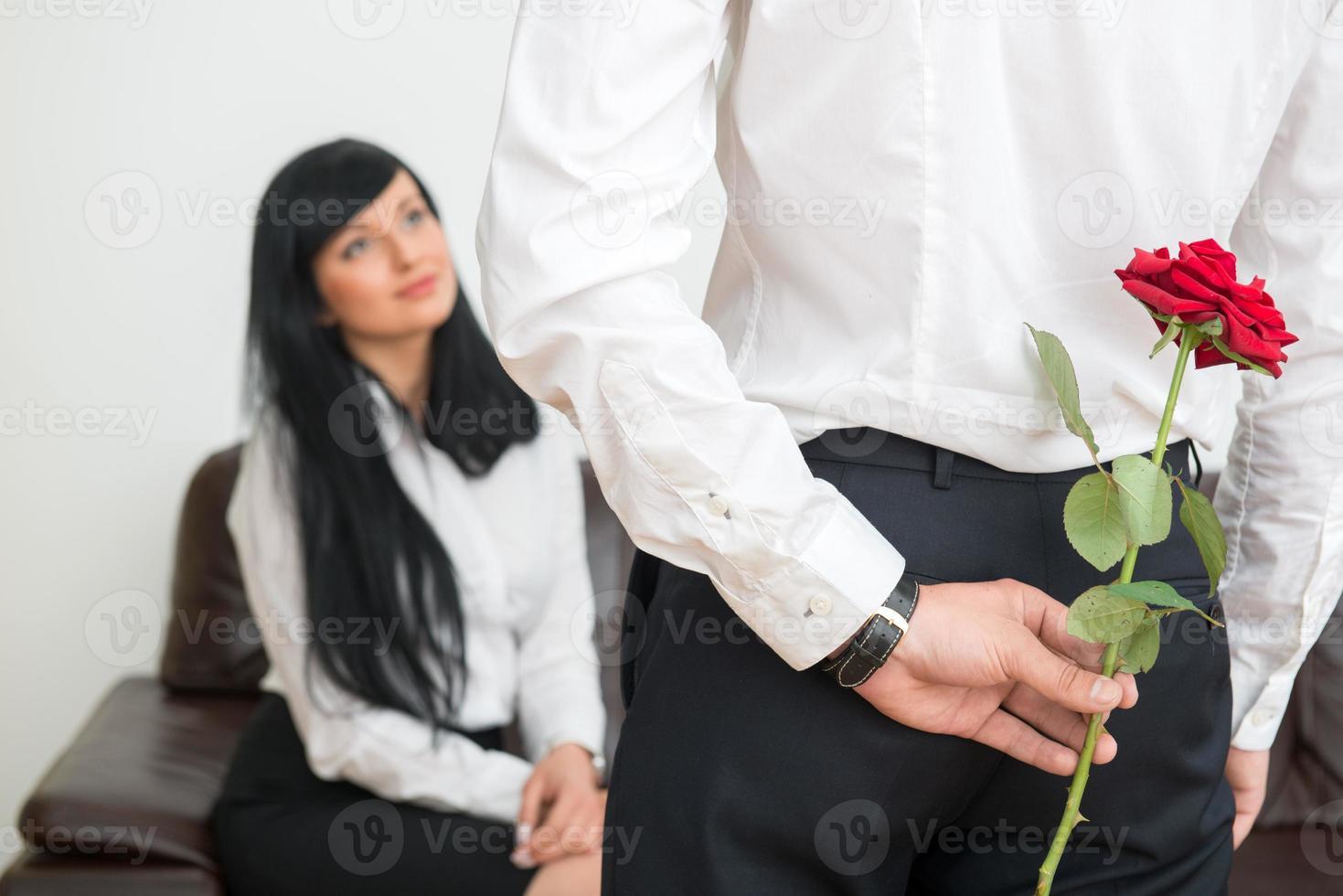 Rückansicht des jungen Geschäftsmannes, der eine Blume für seine versteckt foto