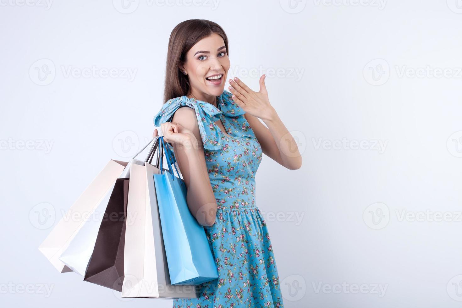 fröhliches junges Mädchen kauft viel Kleidung foto